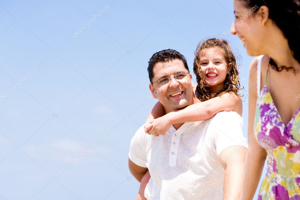 Affectionate couple with daughter looking at camera on the beach — Stock Photo #1369624