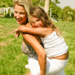 Mother giving piggy ride to daughter — Stock Photo #1370000