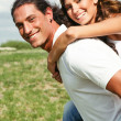 Smiling couple enjoying piggyback ride - Foto Stock