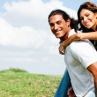 Smiling couple enjoying piggyback ride — Stock Photo