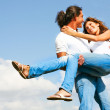 Young man holding woman in his arms — Stock Photo