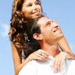 Young smiling couple looking at sky - Stock Photo