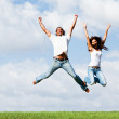 Playful couple jumping high in air — Stock Photo