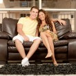 Smiling young couple seated on couch — Stok fotoğraf