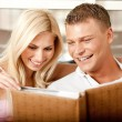 Smiling young couple sharing album — Stock Photo