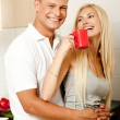 Guy embracing lady in kitchen — Stock Photo #1371053