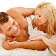 Mid adult lovers smiling in bed - Stock Photo