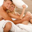 Attractive amorous couple in bedroom - Stockfoto