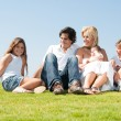 Smiling family relaxing on grass — Stock Photo #1371461