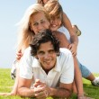 Family piled up on meadow enjoying — Stock fotografie
