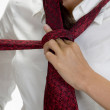 Young pretty woman tying her tie — Stock Photo #1372237