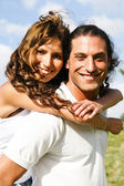 Young man giving piggyback ride to woman — Stock Photo