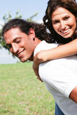 Smiling couple enjoying piggyback ride — Stock Photo