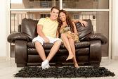 Souriante jeune couple assis sur le canapé — Photo