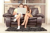 Caucasian couple seated on couch — Stock Photo