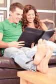 Adorable couple viewing album — Stock Photo