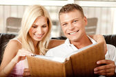 Caucasian couple sharing album — Stock Photo
