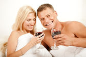 Couple sharing wine in bed — Stock Photo