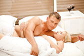 Attractive couple in bedroom — Stock Photo
