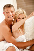 Smiling young couple in bed — Stock Photo