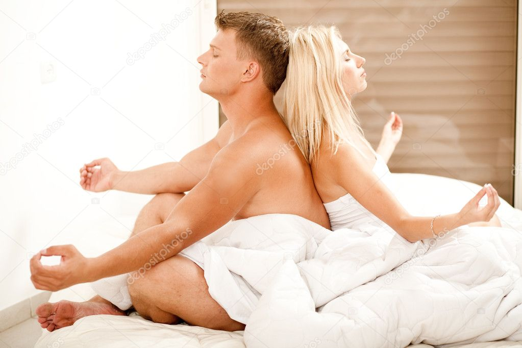 Young man and woman meditating in bed — Stock Photo #1370986