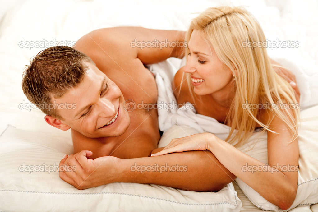 Mid adult lovers having fun and smiling in bed — Stock Photo #1371263
