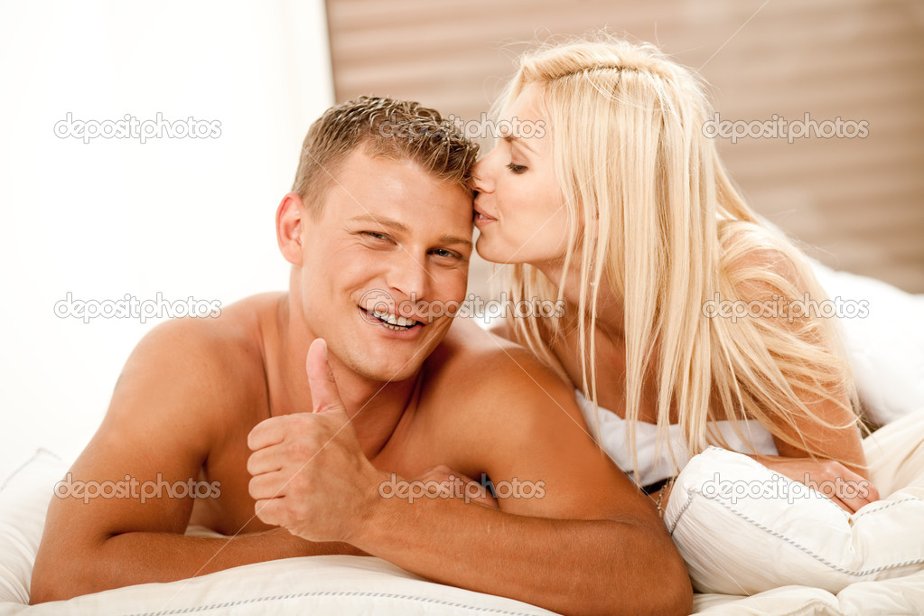Young man showing thumbs up as woman kisses him on head — Stock Photo #1371281