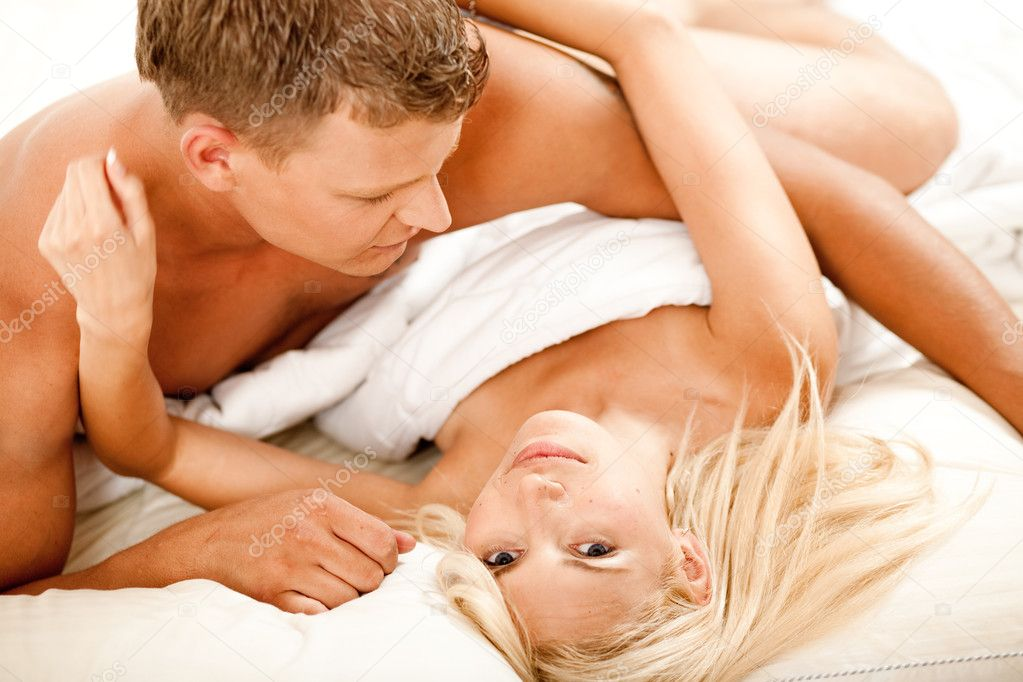 Mid adult couple in bed as woman looks at camera — Stock Photo #1371312