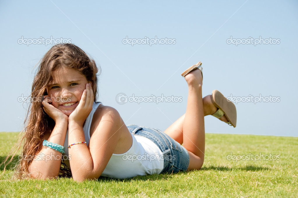 Teen smiling at camera, lying on grass  Stock Photo #1371651