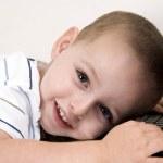 小男孩躺在笔记本电脑上,微笑 — 图库照片