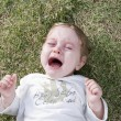 Adorable child crying in the garden — Stock Photo