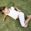 Smiling young cute girl lying on grass — Stock Photo #1649175