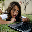 Boy working on laptop, lying on grass — Stock Photo