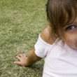 Stock Photo: Smiling little girl sitting on grass