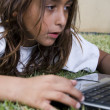 Stock Photo: Young boy playing with laptop