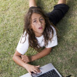 Stock Photo: Little boy lying on grass with laptop