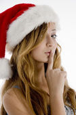 Teenage girl in christmas hat shushing — Stock Photo