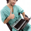 Foto Stock: Doctor working on laptop wishing luck