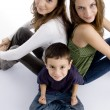 Young kid sitting with his teen sisters — Stock Photo