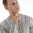 Stock Photo: Thinking young man looking away