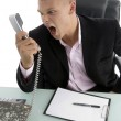 Angry employee shouting on phone — Stock Photo