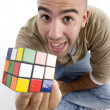 Young guy showing puzzle cube to camera — Stock Photo