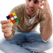 Confused male holding puzzle cube — Stock Photo