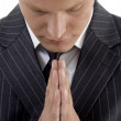 Praying young businessman — Stock Photo