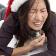 Female in christmas hat playing with pug — Stock Photo