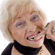 Old woman keeping finger in her mouth — Stock Photo #1659784