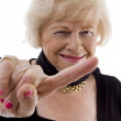 Portrait of cheerful old female pointing - Stock Photo