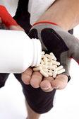 Man taking capsules in hand — Stock Photo