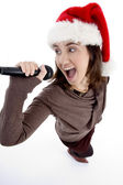 Teen singer with mic and christmas hat — Stock Photo