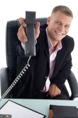 Happy businessman showing receiver — Stockfoto